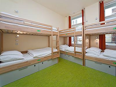 Bunk beds against the wall in a hostel room, with a green carpet