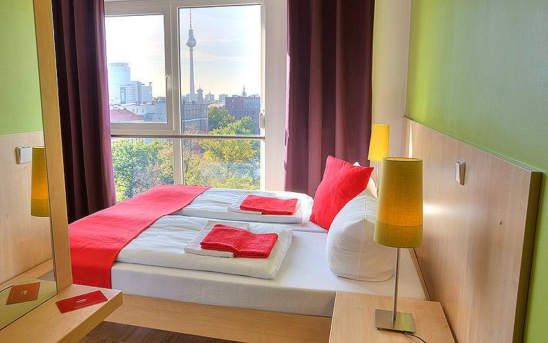 Two single beds topped with red cushions and throws, with a bedside table in the foreground