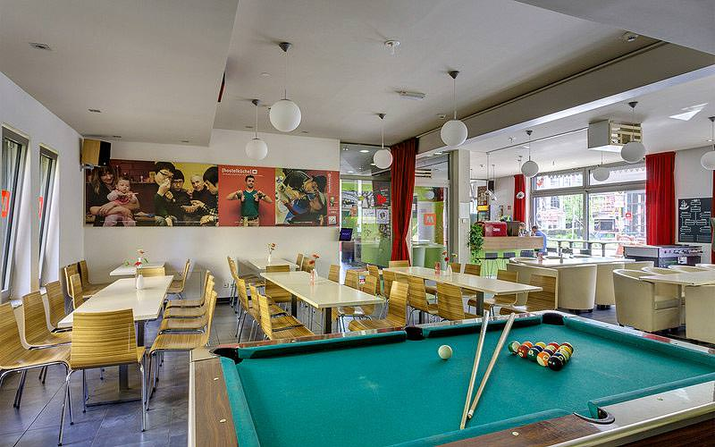 A pool table in the foreground, with tables and chairs in the background