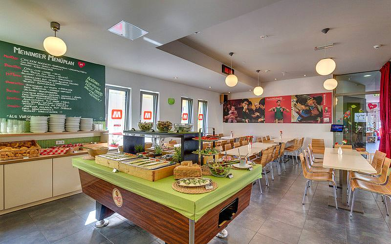 Food on counters in the foreground, with tables and chairs in the background