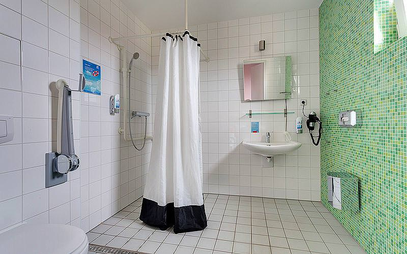 A green tiled bathroom with a walk in shower and sink