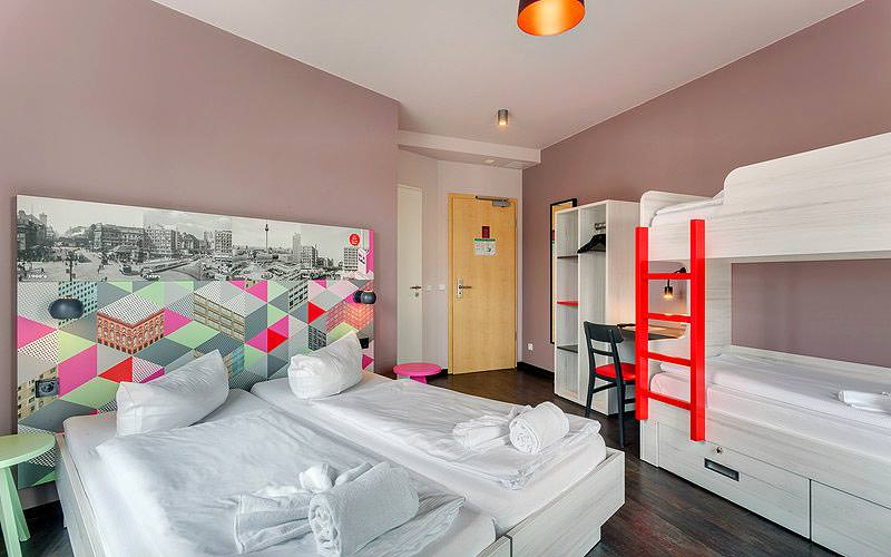 Two single beds topped with towels and cushions, with a bunk bed and storage in the corner