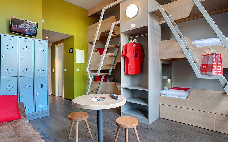 Bunkbeds built into the wall, with a table, two stools and blue lockers in the foreground