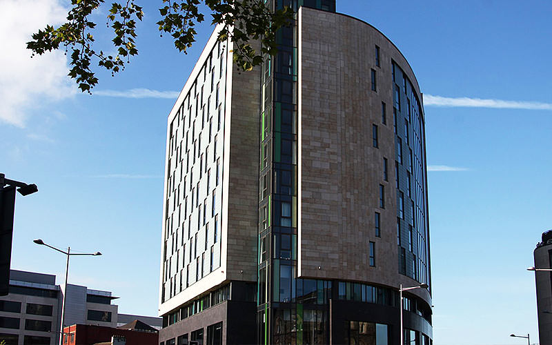 The exterior of Clayton Hotel Cardiff in the day time, under a blue sky
