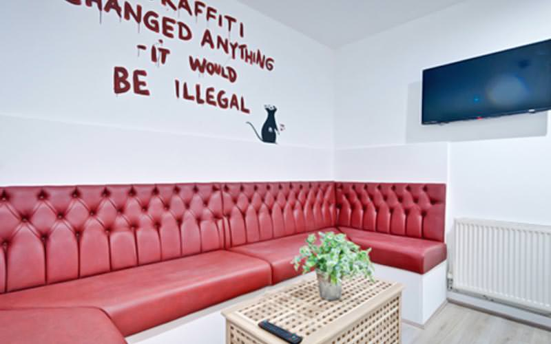 Red sofas along the white wall, underneath a Banksy piece painted on the wall, with a plasma and coffee table in the foreground