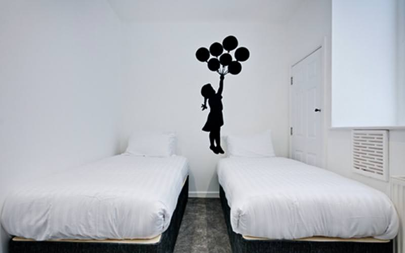 A banksy piece painted on the white wall of a room, with two single white beds