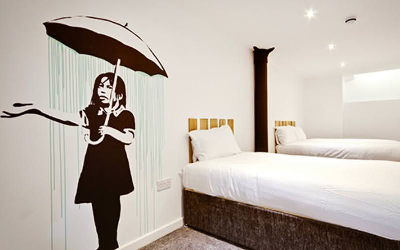 A Banksy piece painted on a white wall, with two white single beds in the corner