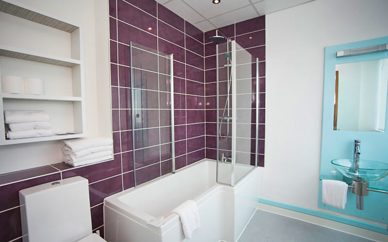 A purple tiled bathroom, featuring a bath and sink