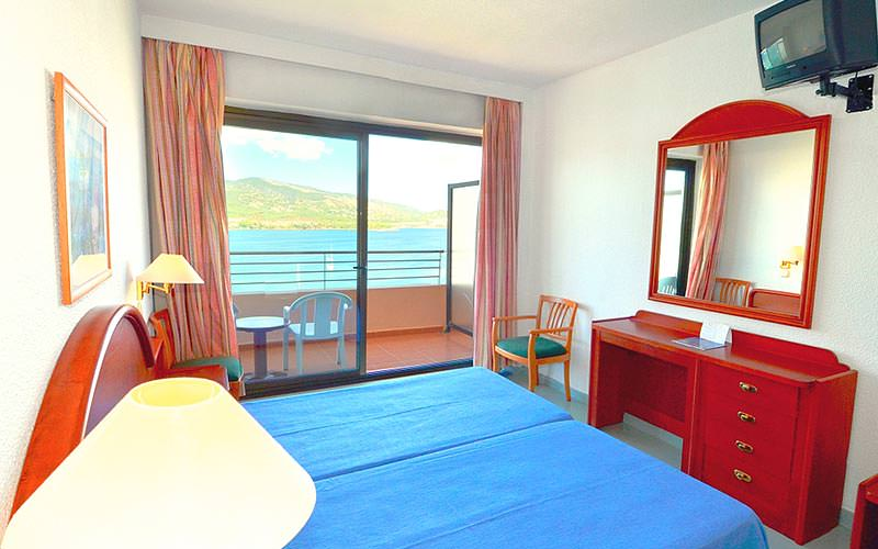 Two blue single beds in a hotel room, facing a red desk and mirror, with a balcony in the background