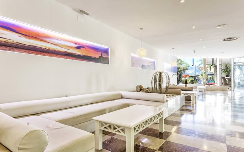 White sofas and tables against a white wall in a hotel lobby