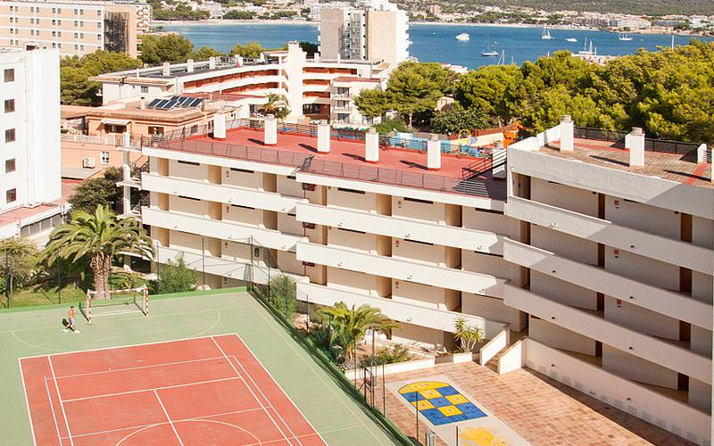 A tennis court with the exterior of TRH Magaluf in the background