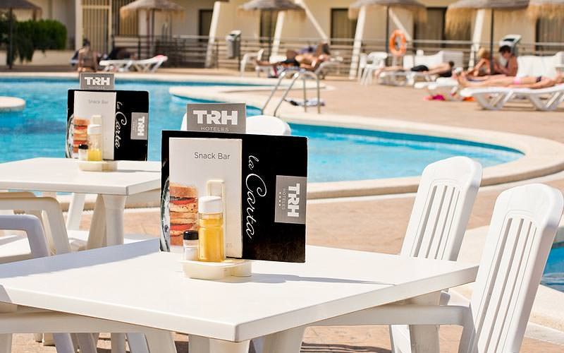 Menus and condiments on outdoor, white tables with people sat around an outdoor pool in the background