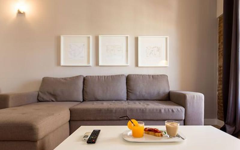 A grey L sofa, facing a white coffee table, topped with a breakfast tray
