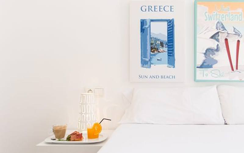Greeze and Switzerland canvases above a double bed, with a breakfast tray on top of a bedside table
