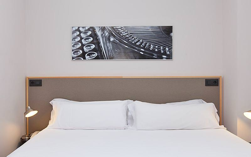 A white double bed with a picture above