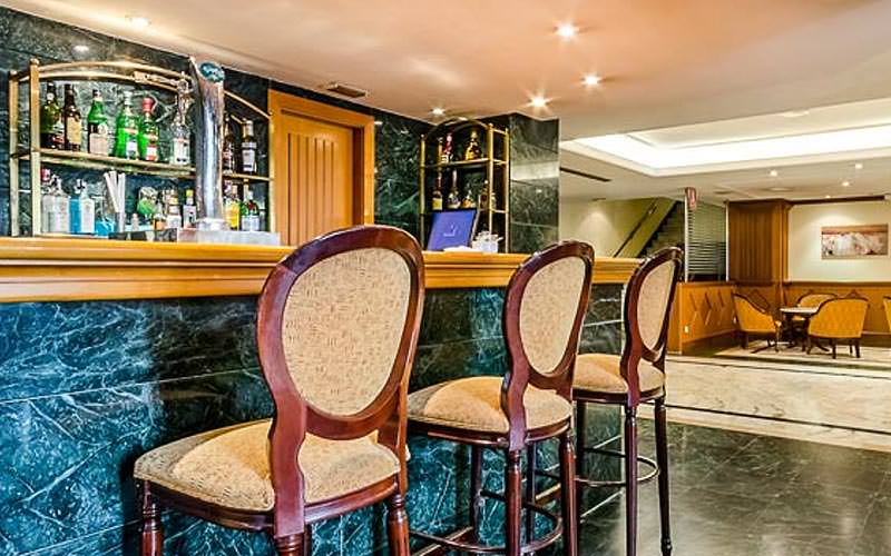 Three bar stools against a marble bar