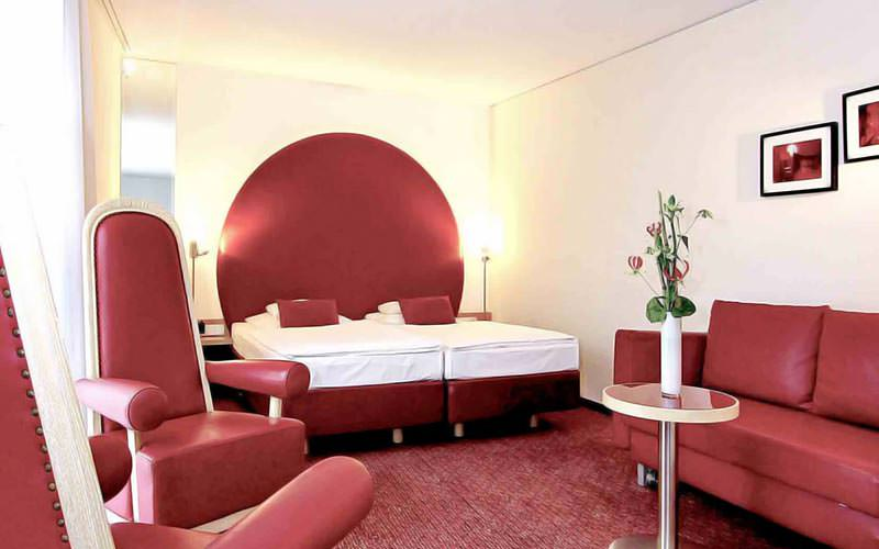 Two single beds with red cushions, with leather red seating in the foreground