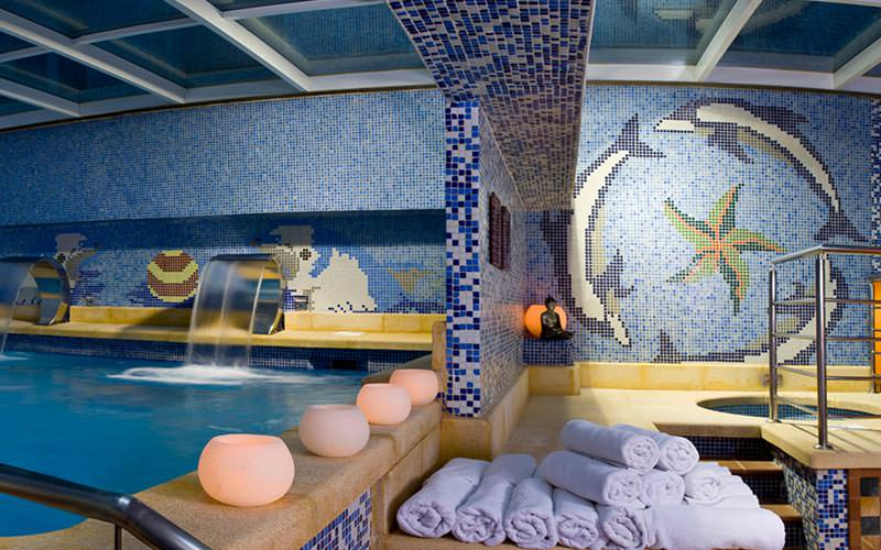 Indoor pool with small lamps around one wall and rolled up towels in the foreground