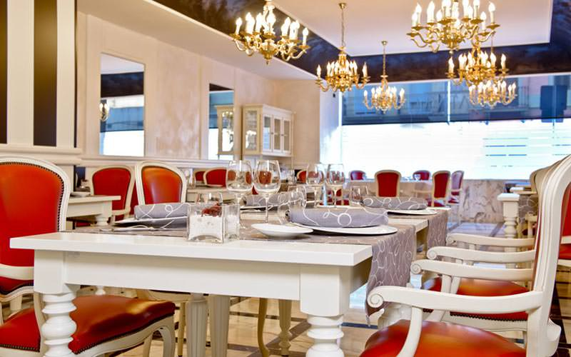 Tables and chairs set up in a restaurant at Hotel Pere IV