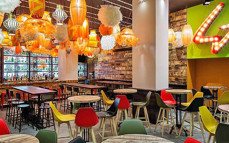 Colourful chairs around tables, underneath hanging lanters, in the restaurant at Generator Barcelona