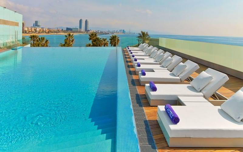 White sun loungers along an outdoor swimming pool on a rooftop terrace
