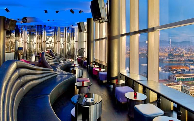 Black leather booths and tables against floor to ceiling windows in the bar at W Hotel, Barcelona