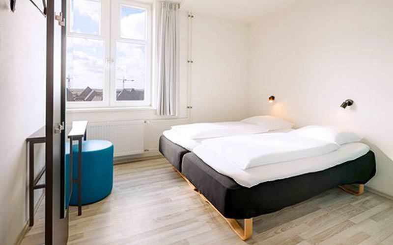 Two single beds in a hotel room, facing a desk and blue stool