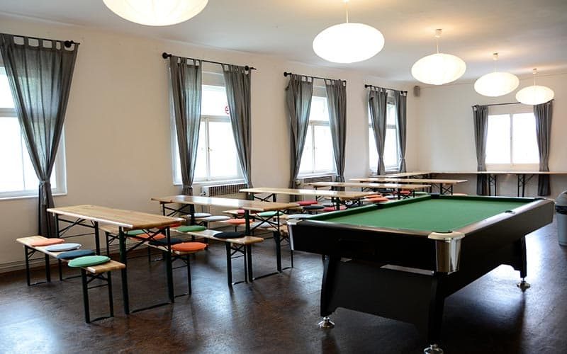 Benches against a wall in a games room, with a pool table in the centre of the room