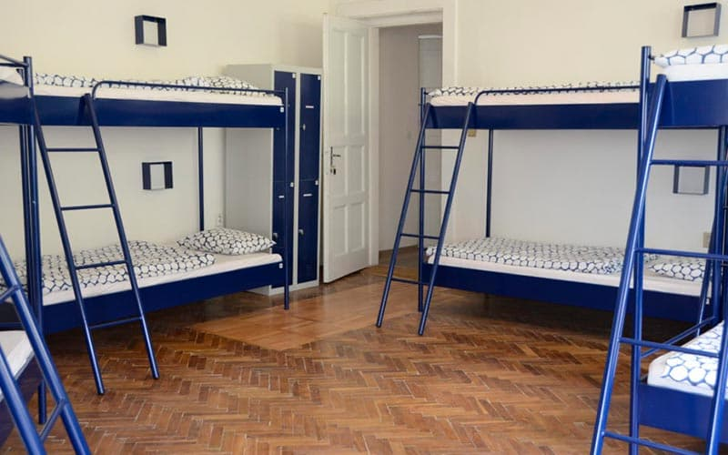 Four blue bunk beds in a dorm room