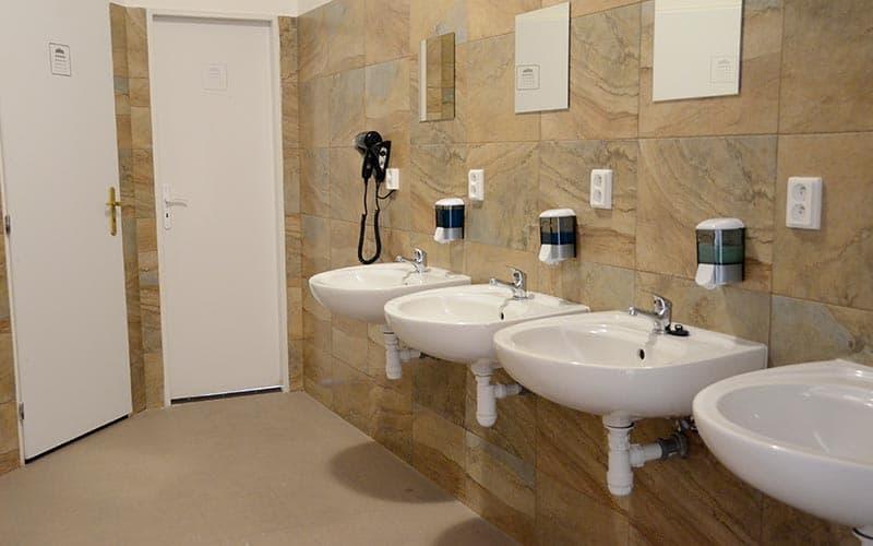 Four sinks against a bathroom wall