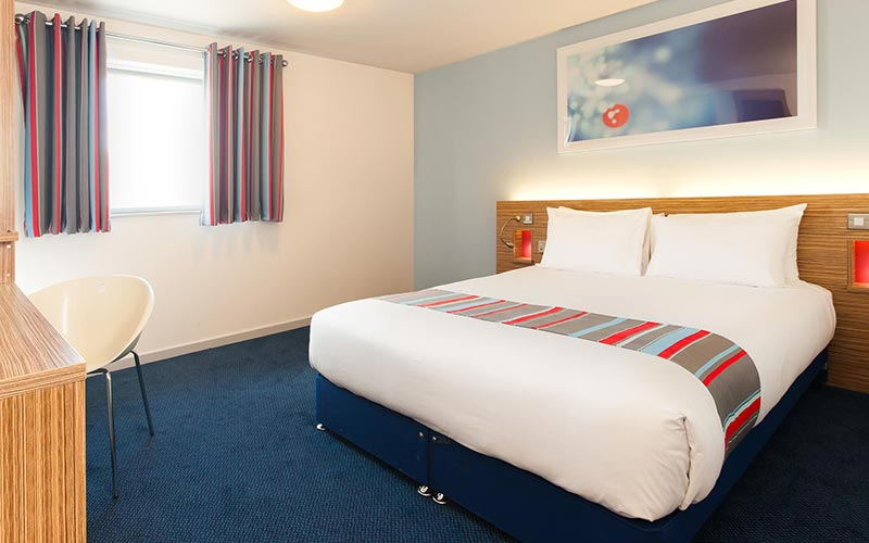 A double bed facing a desk, in a Travelodge hotel room