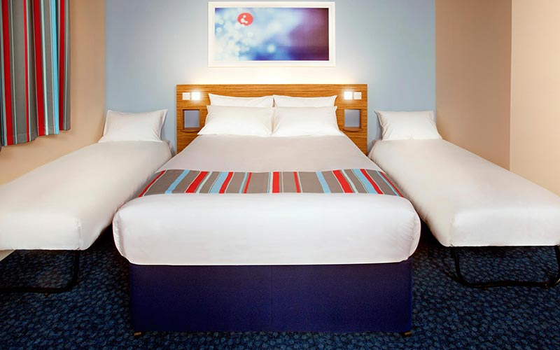 A double bed in a Travelodge hotel room, with two sofa beds on either side