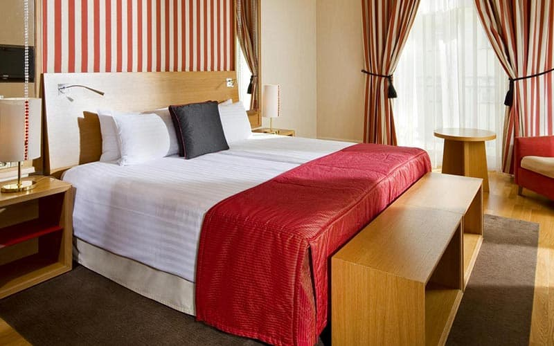 A double bed in a hotel room, topped with a red throw, with a table and chair in the background