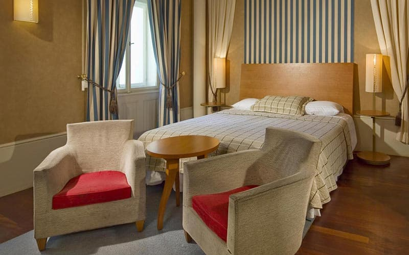 A double bed in a hotel room, with two chairs and a table in between at the foot of the bed