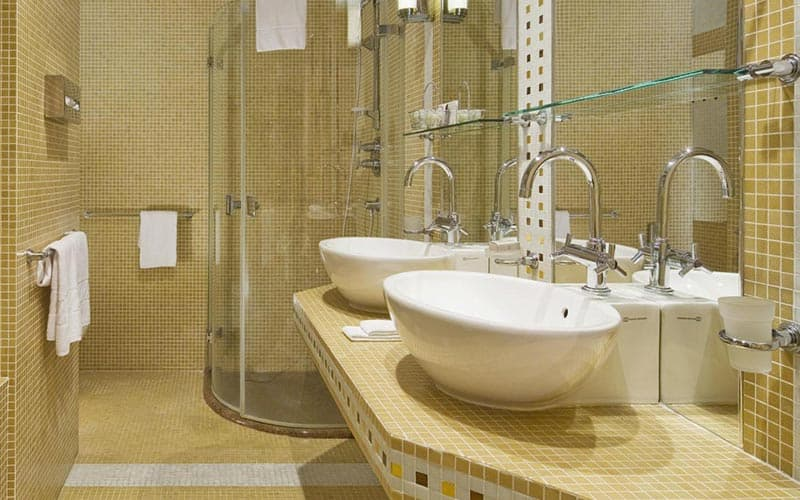A tiled bathroom with a shower in the back, and two sinks on a shelf in the foreground