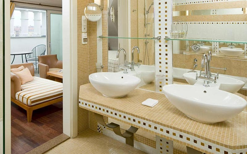A hotel bathroom featuring two sinks on a shelf, with a sofa and chair visible through an open door in the corner