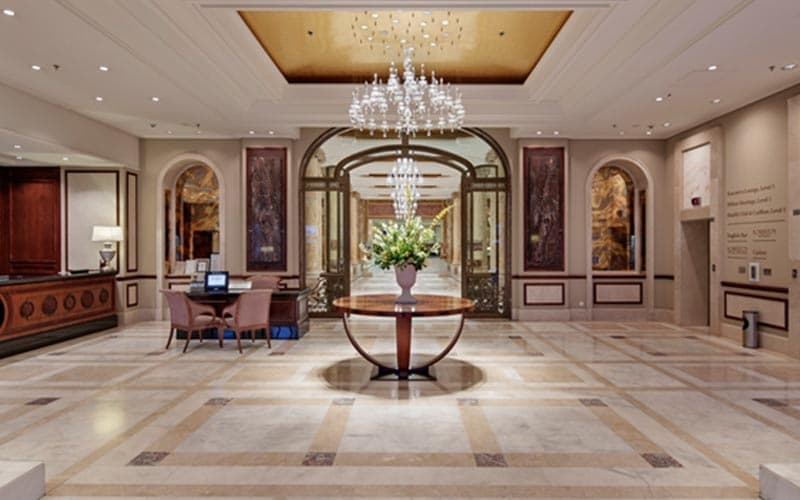 The lobby of Athenee Palace Hilton Bucharest, with flowers on a table in the centre of the room
