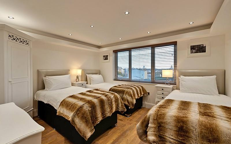 Three single beds in a room, topped with fur throws, with a bedside table in the foreground