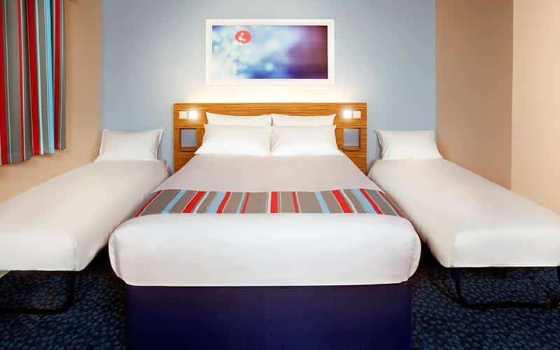 A double bed topped with a striped throw, with two single beds on either side, in a hotel room