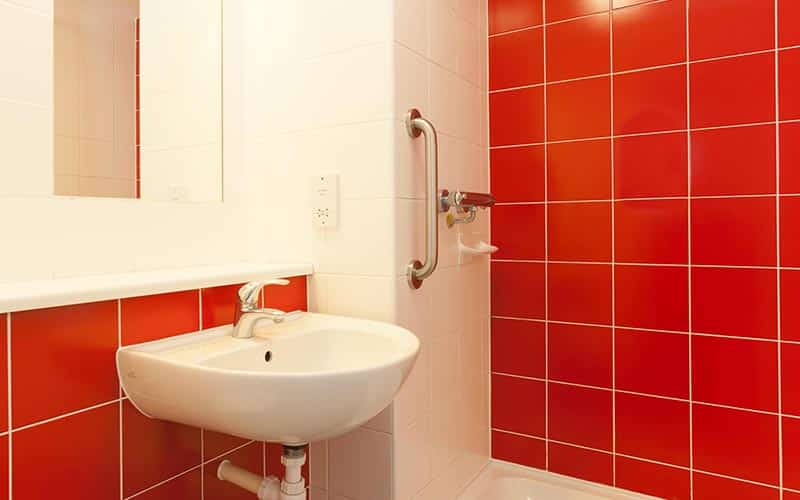 A red tiled bathroom in a hotel