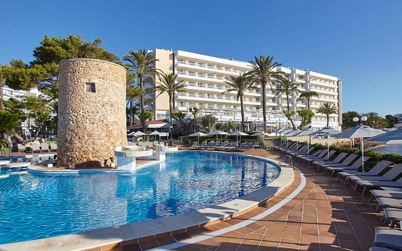 An outdoor pool surrounded by sun loungers, with the Hotel Torre del Mar in the background