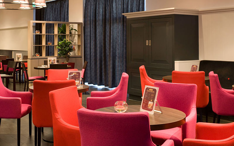 Pink and red chairs around circular tables in a hotel lobby
