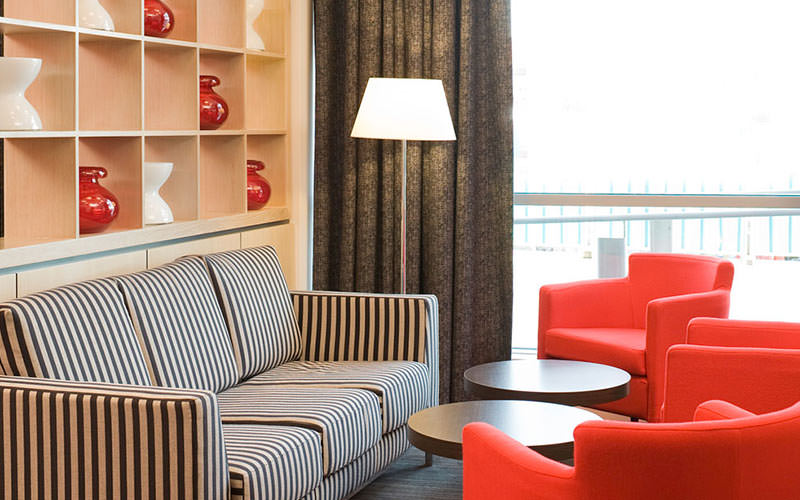 Striped sofa and red chairs around a circular table