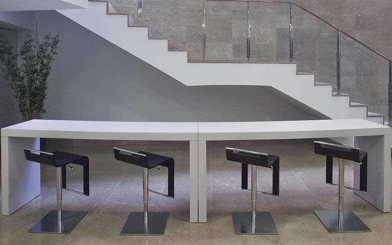Four black stools lined up in front of a white table, with a staircase in the back