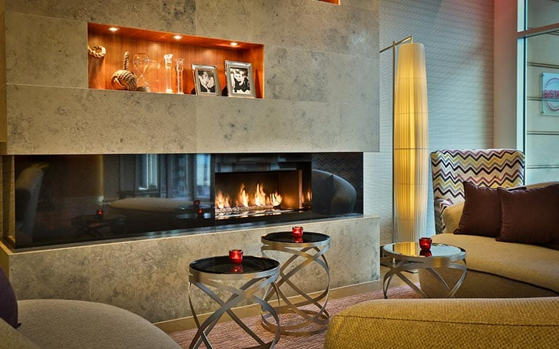 Sofas in front of a fire in the wall at Jurys Inn Prague