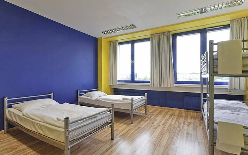 A room with blue and yellow walls, with two single beds and a bunk bed in