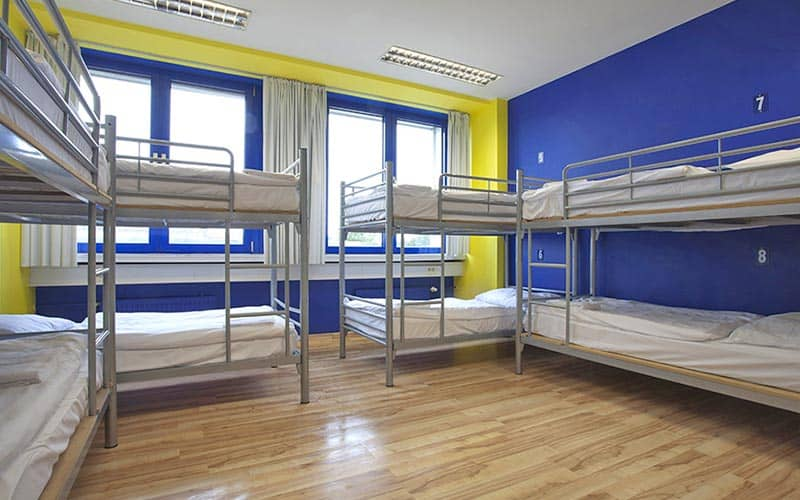 Four bunk beds lining the rooms of a hostel