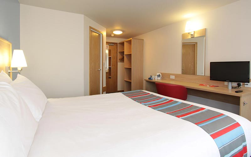 A double room at Travelodge Bournemouth, with a bed facing a desk