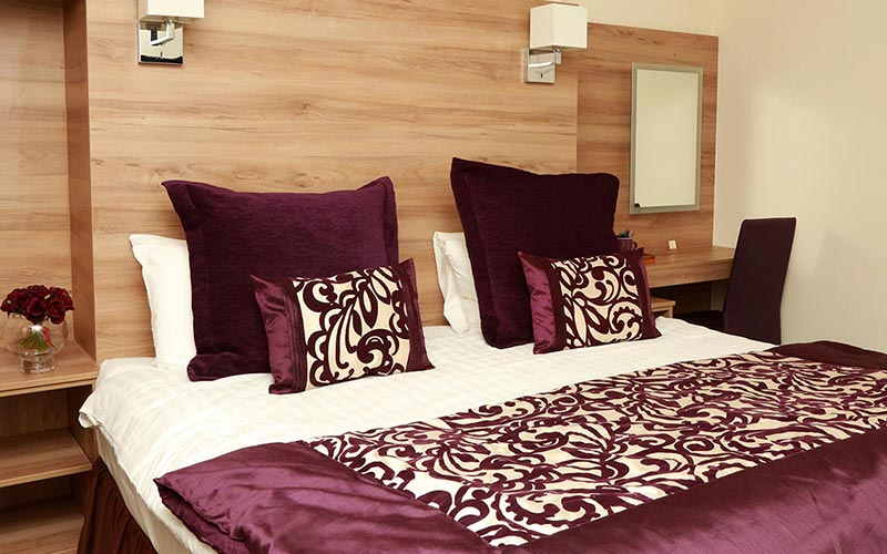 A double bed with purple and cream bedding