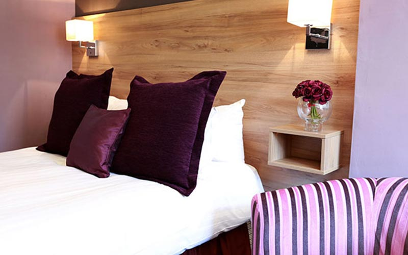 A double room with purple cushions on the bed and roses on the bedside table
